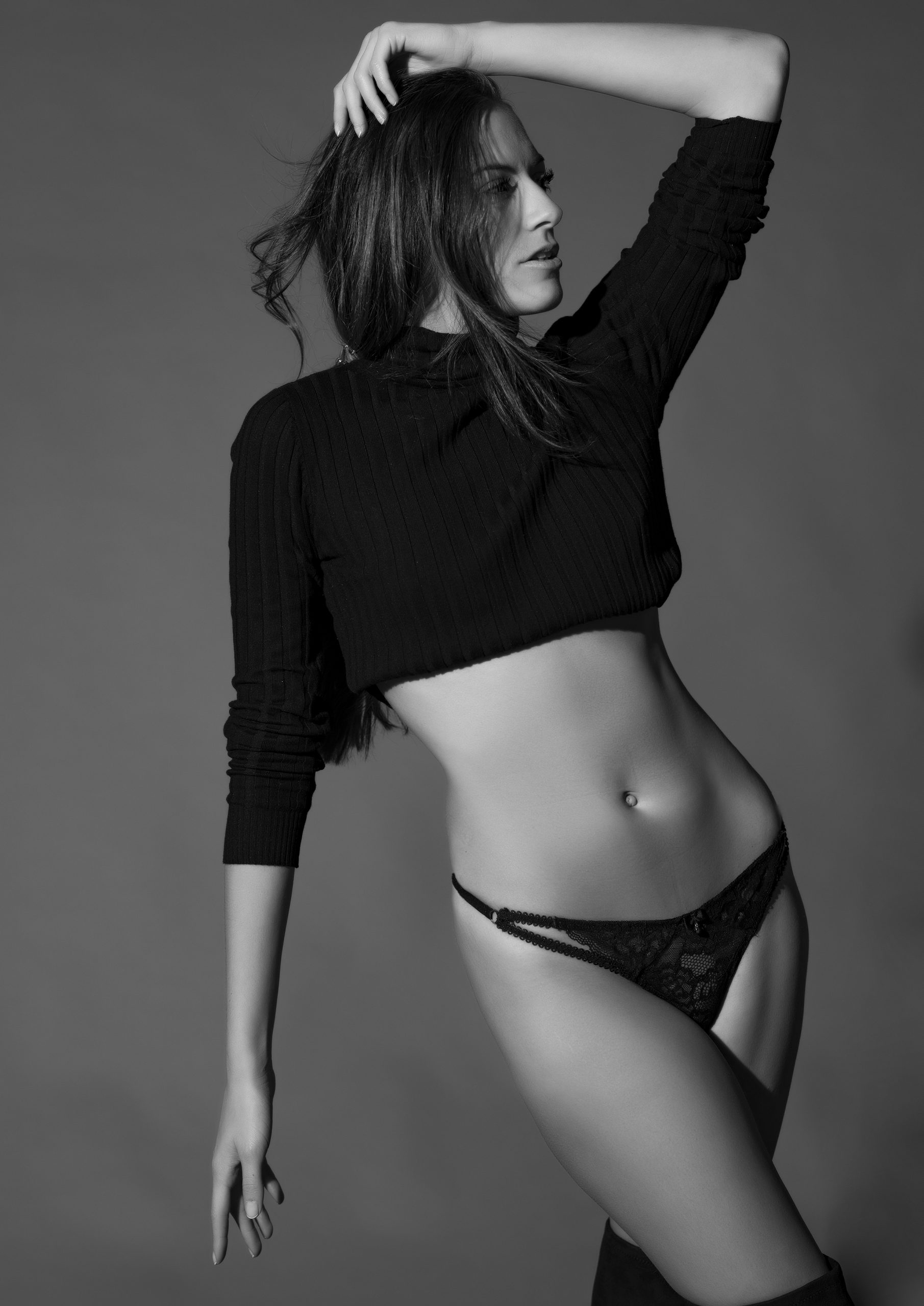 Black and white fashion photo of a model wearing black knickers and short black jumper