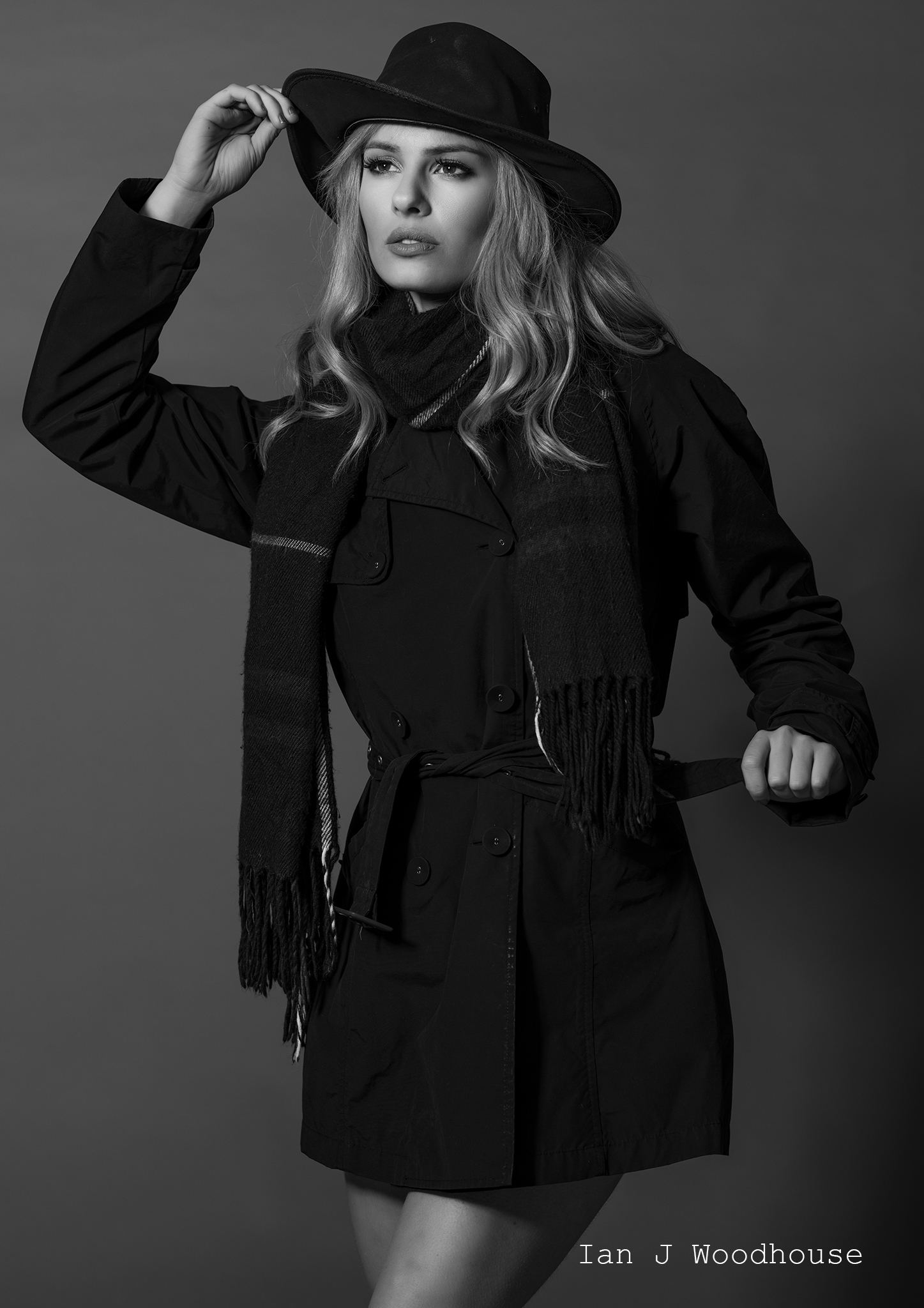 Studio black and white fashion shoot, model wearing a black rain coat and hat